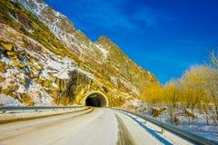 LOFOTEN, NOORWEGEN, 10 APRIL, 2018: De mening van bevroren straat met een informatief teken bij gaat van een tunnel in Skjelfjord Royalty-vrije Stock Afbeelding