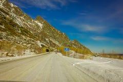 LOFOTEN, NOORWEGEN, 10 APRIL, 2018: De mening van bevroren straat met een informatief teken bij gaat van een tunnel in Skjelfjord Royalty-vrije Stock Foto's