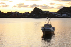 Lofoten' winter darkness. Mortsund i Lofoten harbour, with a small boat for cod fishing, in december's pale light stock image