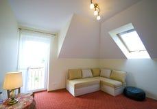 Loft bedroom. A loft room with balcony door and a corner couch stock photos