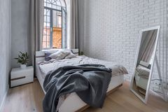 Loft bedroom with brick wall. Loft bedroom with white brick wall, double bed and mirror royalty free stock photography