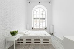 Loft bedroom with brick wall. Loft bedroom with white brick wall, pallet bed and half circle window stock photos