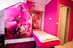 Loft bedroom conversion with orchid theme. Loft bedroom conversion with pink wall and decoration with  mainly pink orchids and with bed dropping out from a Royalty Free Stock Photo