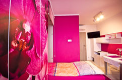 Loft bedroom conversion with orchid theme. Loft bedroom conversion with pink wall and decoration with  mainly pink orchids and with bed dropping out from a Stock Photo