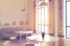 Loft cafe corner with round tables toned. Corner of a modern loft cafe interior with woodne walls and concrete floor, round tables and chairs and a gray sofa Stock Image