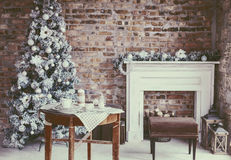 Loft Christmas room. Winter home decor. Christmas tree in loft interior against brick wall. Old vintage furniture Stock Image