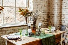 Loft el interior con la pared de ladrillo, la tabla y las sillas Imágenes de archivo libres de regalías