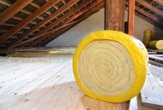 Loft Insulation. A roll of insulating glass wool on an attic floor stock photos