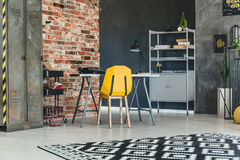 Loft interior with brick wall. Desk, yellow chair and bookcase Royalty Free Stock Photos