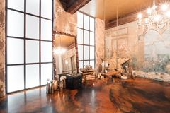 Loft interior with mirror, candles, brick wall, large window, living room, coffee table in modern design. Interior with fireplace, candles, skin of cows, brick Royalty Free Stock Image