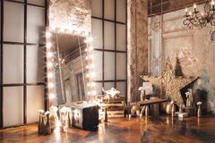 Loft interior with mirror, candles, brick wall, large window, living room in modern design.  Royalty Free Stock Photos