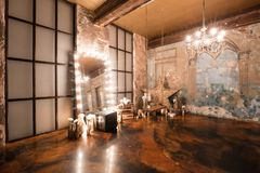 Loft interior with mirror, candles, brick wall, large window, living room in modern design.  Royalty Free Stock Photo