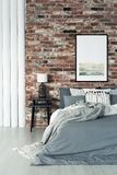 Loft interior with painting. Grey bedding on bed in loft interior with painting on red brick wall and lamp on black stool royalty free stock photos