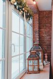 Loft interior. Window view. Christmas time. The interior of the loft. View of a window with red brick wall and Christmas decorations Royalty Free Stock Images