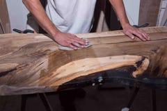 Loft la tabla con la resina de epoxy en el taller resina negra con las piedras dentro manos del creador ilustración del vector