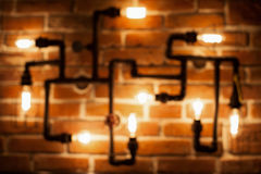 Loft lamp with Edison lamps in defocus. On a brick wall background Stock Photography
