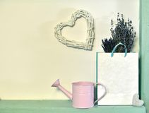 Cute watering can with lavender flowers in paper bag and heart shape on white wall stock images