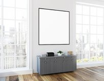 Loft living room gray dresser, poster side view. Loft living room interior with white walls, a wooden floor, a gray chest of drawers with a square framed poster Stock Images