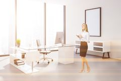 Loft manager office corner, poster, businesswoman. Businesswoman in manager office corner with peach walls, concrete floor, panoramic windows, a large computer royalty free stock photography