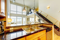 Loft modern apartment with wood kitchen and staircase. Royalty Free Stock Photography