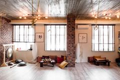 Loft room for fitness and relaxation, relaxation with brick walls and windows, gym, tea. stock images