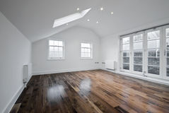 Loft room with roof window. Unfurnished room with roof windows and hard wood floor Royalty Free Stock Photography