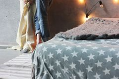 Loft style bedroom, bed with grey blanket and couple in background. Loft style bedroom, bed with grey blanket and man and woman in the background Stock Images