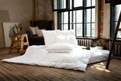 Loft style bedroom interior design. White blanket and pillows. royalty free stock photography