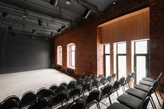 Loft style. Hall with black chairs for webinars and conferences. A huge room with large Windows, surrounded by brickwork. And parquet floors. For film and Stock Images