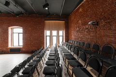 Loft style. Hall with black chairs for webinars and conferences. A huge room with large Windows, surrounded by brickwork. And parquet floors. For film and Royalty Free Stock Image