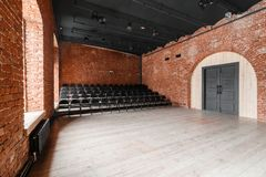 Loft style. Hall with black chairs for webinars and conferences. A huge room with large Windows, surrounded by brickwork. And parquet floors. For film and Stock Photography