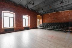Loft style. Hall with black chairs for webinars and conferences. A huge room with large Windows, surrounded by brickwork. And parquet floors. For film and Royalty Free Stock Photos