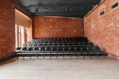Loft style. Hall with black chairs for webinars and conferences. A huge room with large Windows, surrounded by brickwork. And parquet floors. For film and Stock Photos