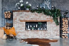 Loft style. Interior with brick fireplace, candles, greenery, modern chair skin of cows, grey wall, firewoods, modern design. royalty free stock photos
