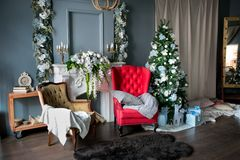 Loft-style room with a red and brown armchair, a white fireplace with flowers, decorated for Christmas. Gifts at the Christmas stock photos