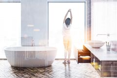 Loft white bathroom interior, woman. Woman in a loft bathroom interior with white walls, a wooden floor, a white bathtub and a round sink. 3d rendering mock up stock photography