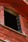 Loft Window. Looking up at the spooky appearance of the dark inside of a barn loft opening Royalty Free Stock Photos