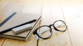 Loft workspace with stationaries on wooden table. Royalty Free Stock Photo