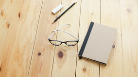 Loft workspace with stationaries on wooden table. Royalty Free Stock Images