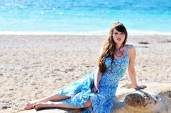 On the log. Young woman sitting on the log on the beach Royalty Free Stock Images
