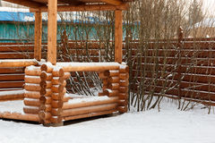 Log arbor in bushes in the snow. Log arbor in the bushes in the snow royalty free stock image