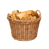 Log basket. Traditional wicker log basket with oak logs isolated against a white background Royalty Free Stock Photography