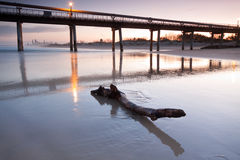 Log on beach at twilight with pier and the city. In background Royalty Free Stock Images
