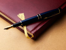 Log book. Old fashioned diary or log book with a fountain pen  on a grungy background Royalty Free Stock Photo