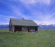 Log Cabin. View of a log cabin with long grass in the foreground and mountains in the background Royalty Free Stock Photography