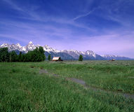 Log Cabin. View of a log cabin with long grass in the foreground and mountains in the background Stock Images