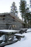 Log Cabin. Wooden log cabin with snow covered rustic benches and tables in the swedish mountains Stock Photography