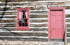 Log Cabin. Red doors and windows on an old log cabin Royalty Free Stock Photos