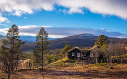 Log cabin in autumn. With blue sky and clouds Stock Image