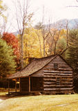 Log Cabin among Autumn Trees. Old Log Cabin nestled among colorful autumn trees stock images
